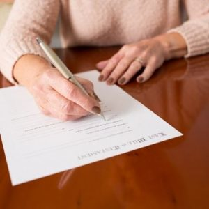 Woman signing her will - why you need a will and what happens when you don't have one