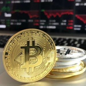 No, I'm Not Investing in Bitcoin - image of bitcoin with computer screen in background.