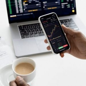 3 Ways to Start Investing in the Stock Market - hand holding phone showing stock prices