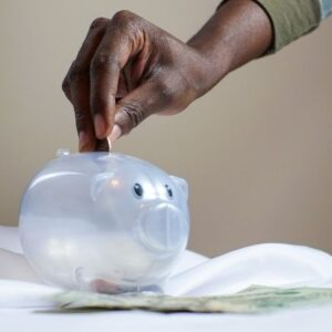 Living Below Your Means - Hand putting change into a piggy bank